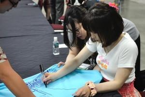 Shimoda signs an Idolmaster concert T-shirt